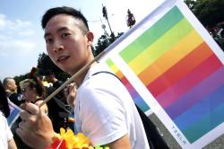 In this Oct. 27, 2018 file photo, a participant carries the rainbow flag during the annual gay and lesbian parade, organized by Taiwan LGBT Pride, in Taipei, Taiwan