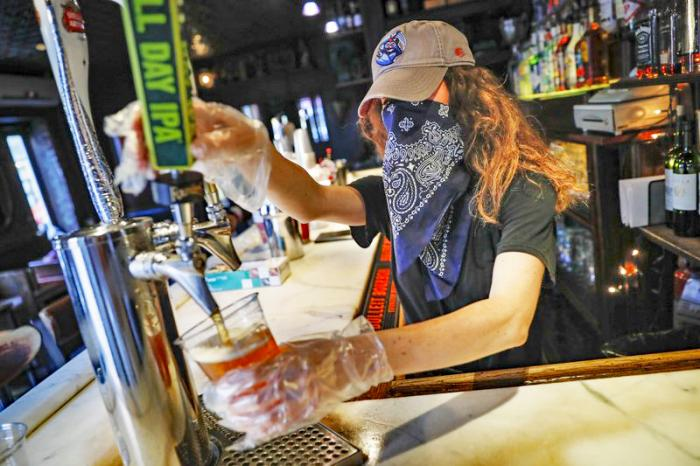 In this June 22, 2020, file photo, a bartender pours a beer for a customer at Shade Bar NYC in New York