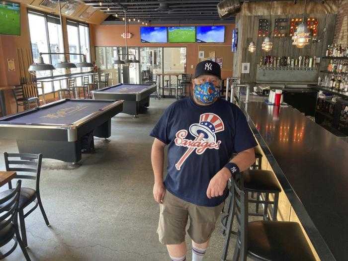 Flattop Pizza bartender Mike Miller poses for a photo at the restaurant in downtown Anchorage, Alaska, Wednesday, July 1 2020, the same day Alaska residents began receiving their share of the state's oil wealth