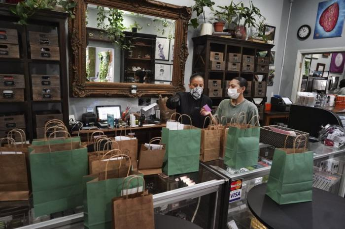 In this April 16, 2020, file photo, budtenders wearing protective masks prepare orders for customers to pick up at the Higher Path cannabis dispensary in the Sherman Oaks section of Los Angeles