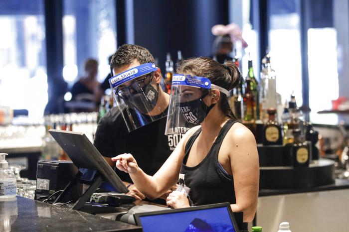 Bartenders were masks and face shields as they work at Slater's 50|50 in Santa Clarita, Calif.