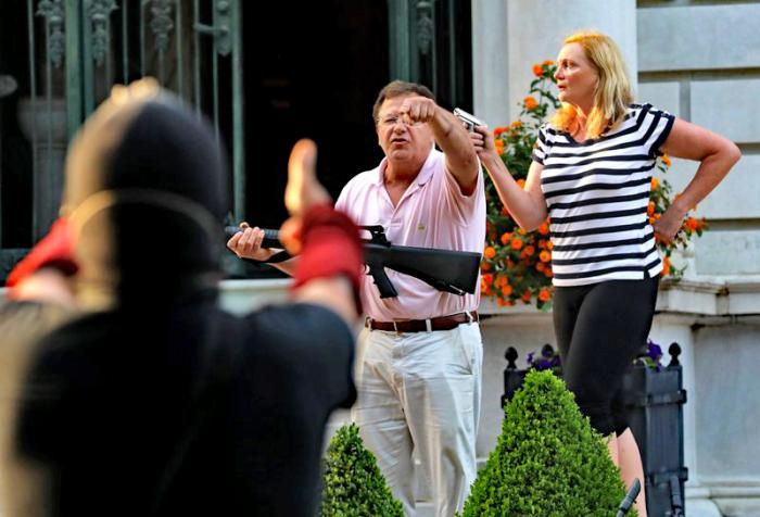 Armed homeowners standing in front their house along Portland Place confront protesters marching to St. Louis Mayor Lyda Krewson's house Sunday, June 28, 2020, in the Central West End of St. Louis