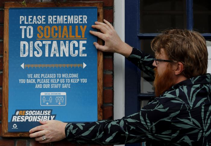 Owner Are Kjetil Kolltveit from Norway put signs in place instructing on social distancing at the Chandos Arms pub in London