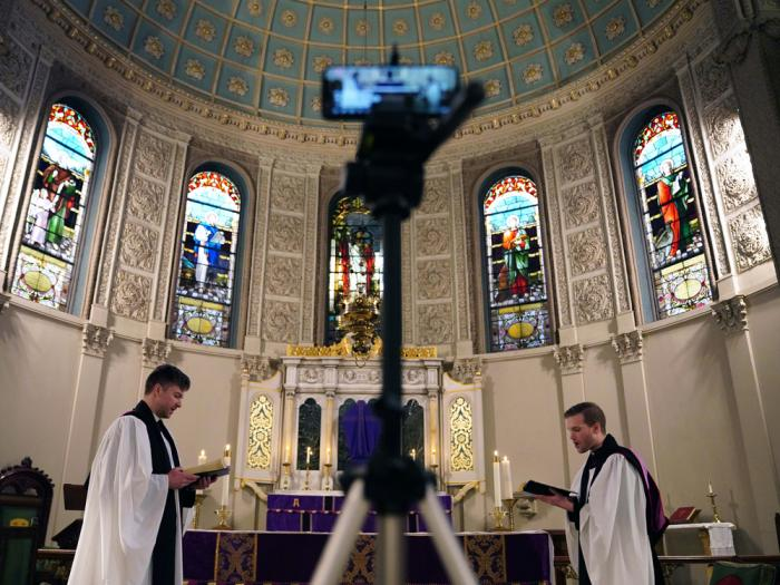In this March 29, 2020 file photo, the Rev. Steven Paulikas, right, and curate Spencer Cantrell deliver an Evening Prayer service over Facebook Live in the Brooklyn borough of New York, amid the global COVID-19 coronavirus pandemic