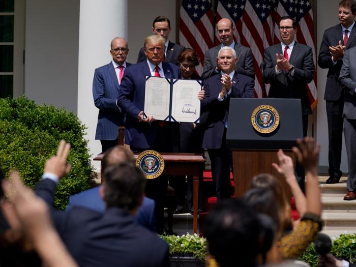 In this June 5, 2020 file photo, President Donald Trump poses for a photo after signing the Paycheck Protection Program Flexibility Act during a news conference in the Rose Garden of the White House in Washington