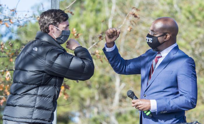 Jon Ossoff, left, and Raphael Warnock exchange elbow bumps during a campaign rally in Augusta, Ga., Monday, Jan. 4, 2021.