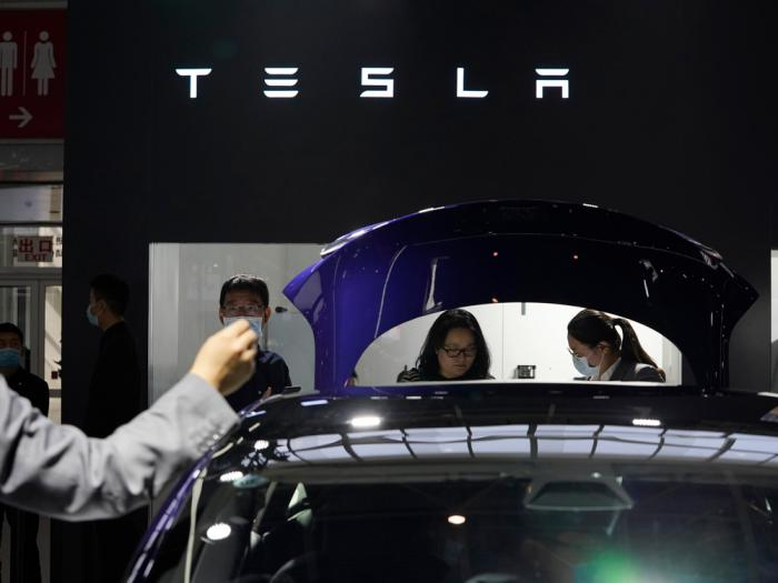 In this Sunday, Sept. 27, 2020, file photo, attendees wearing masks to protect from the coronavirus look at cars at the Tesla booth during the Auto China 2020 show in Beijing