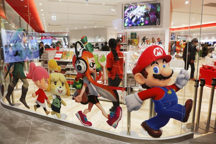 Nintendo characters, including Mario, right, are seen on a glass of its official store in Tokyo.