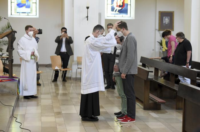 Vicar Wolfgang Rothe, center, blesses two men during a Catholic service with the blessing of same-sex couples in St Benedict's Church in Munich.