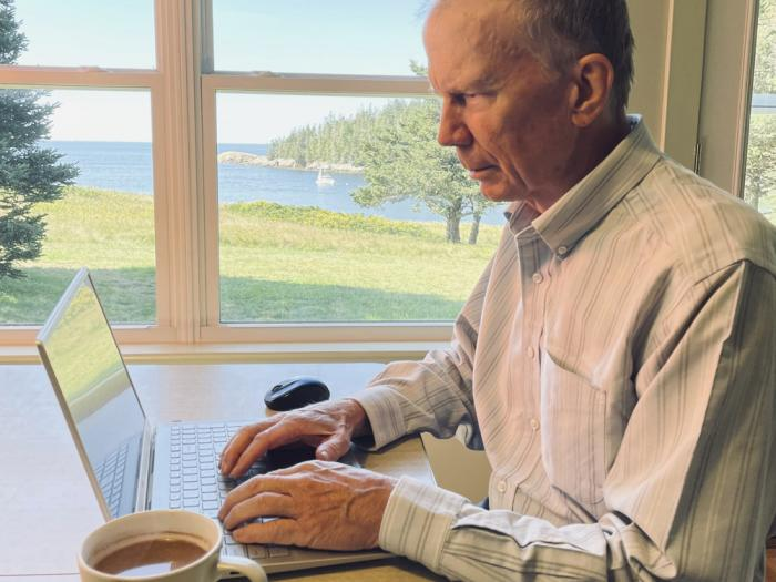 In this photo provided by Donna Hopkins, Charlie Hopkins looks at his laptop computer at his home on Isle au Haut, Maine, on Sept. 4, 2021