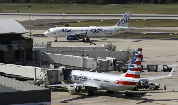 A JetBlue Airbus A320 taxis to a gate Wednesday, Oct. 26, 2016, after landing as an American Airlines jet is seen parked at its gate at Tampa International Airport in Tampa, Fla.